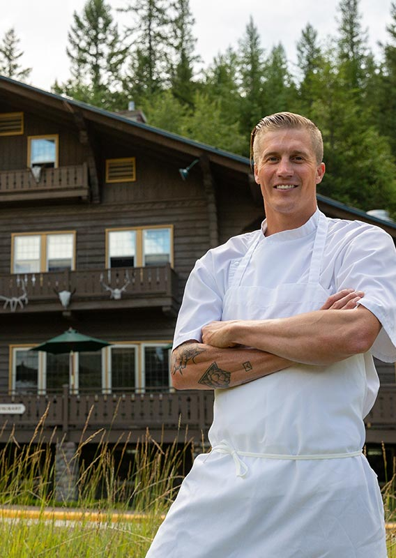 A chef stands in front of the wooden Belton Chalet