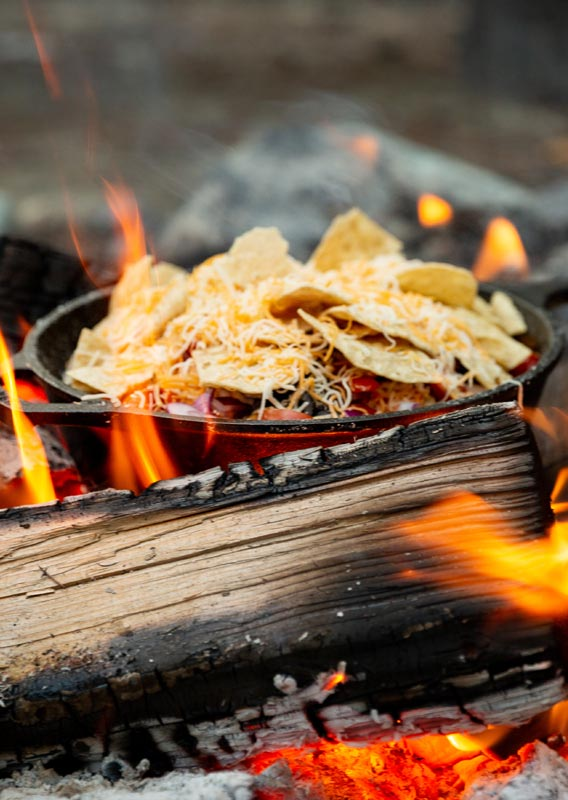 A cast iron pan of nachos cooking over a campfire