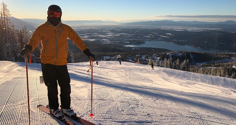 A skier in a yellow jacket at the top of a ski hill.
