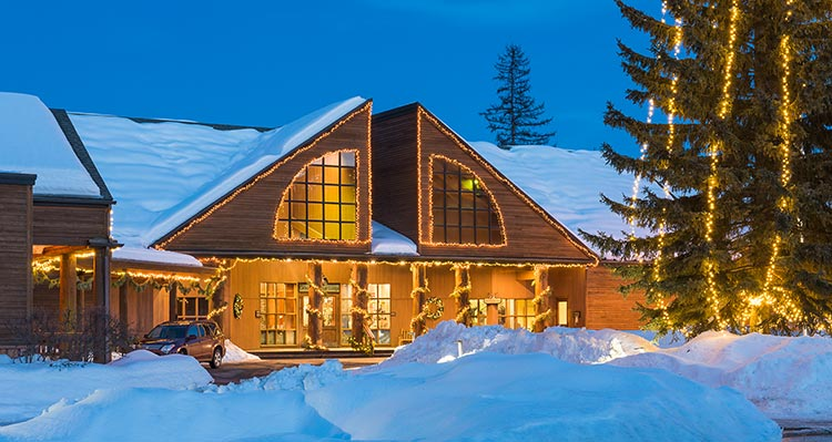 The Grouse Mountain Lodge covered in snow and decorated with Christmas lights.