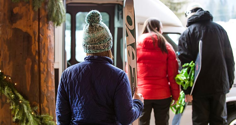 Skiers get onto a bus outside of Grouse Mountain Lodge