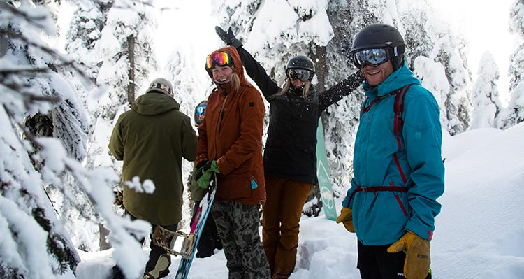 A group of friends in ski gear stand among snow-covered trees