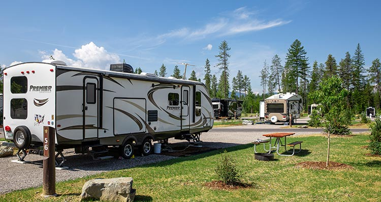 A camping trailer set in an RV park around trees.