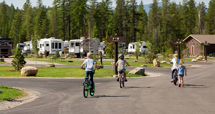 A group of kids ride their bikes through an RV park.