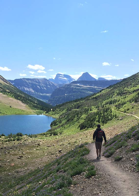 A hiker walks on a trail towards a small lake between tree-covered mountains.