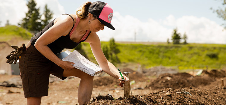 A woman with a clipboard measures the temperature of compost