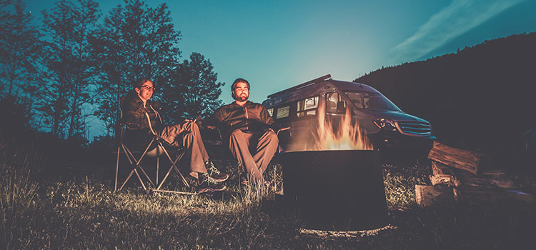 A couple sits by a campfire at dusk with a camper van in the background