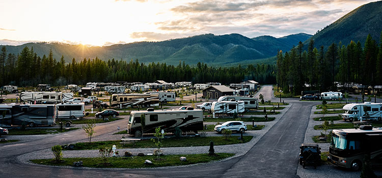 a view of an RV park at sunset with mountains in the background