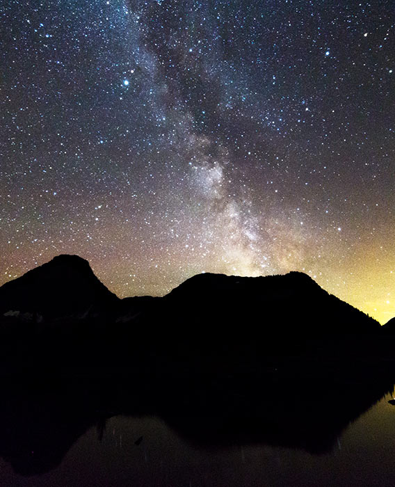 A landscape view of mountains with a night sky filled with stars and the milky way