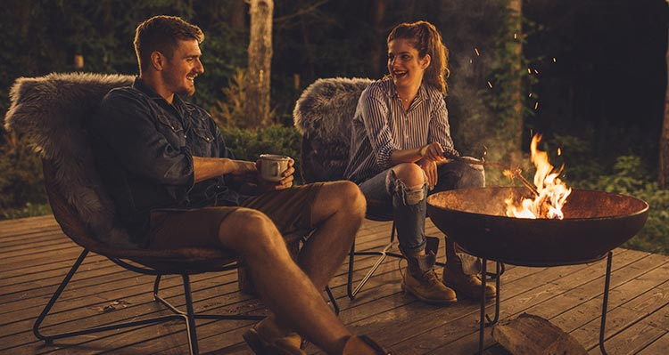 Two people sit around a campfire.