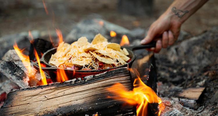 A cast-iron pan of nachos roasting on a fire.